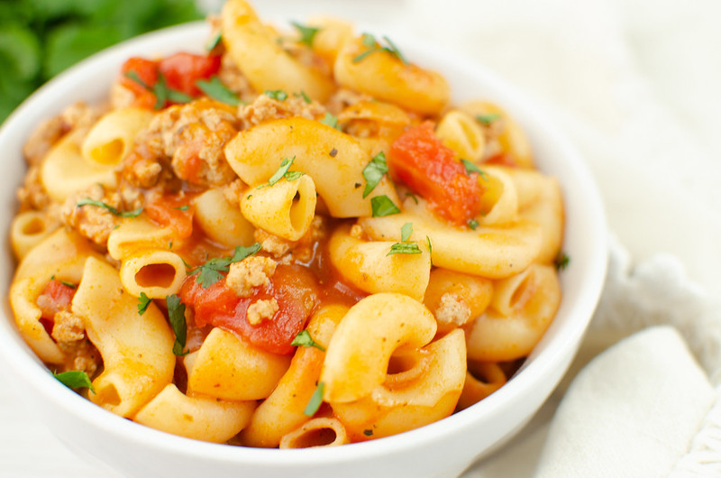 Pasta with ground turkey and tomato sauce in a white bowl; parsley sprinkled on top and in the background