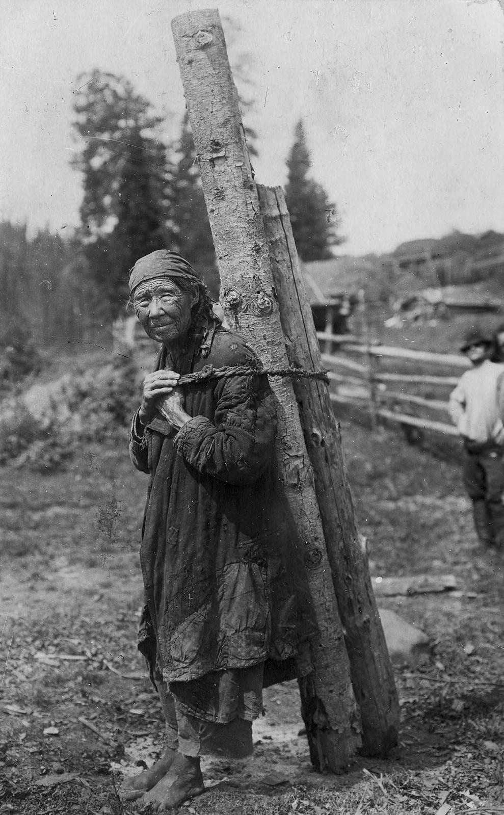 Старуха-шорка заготавливает дрова.