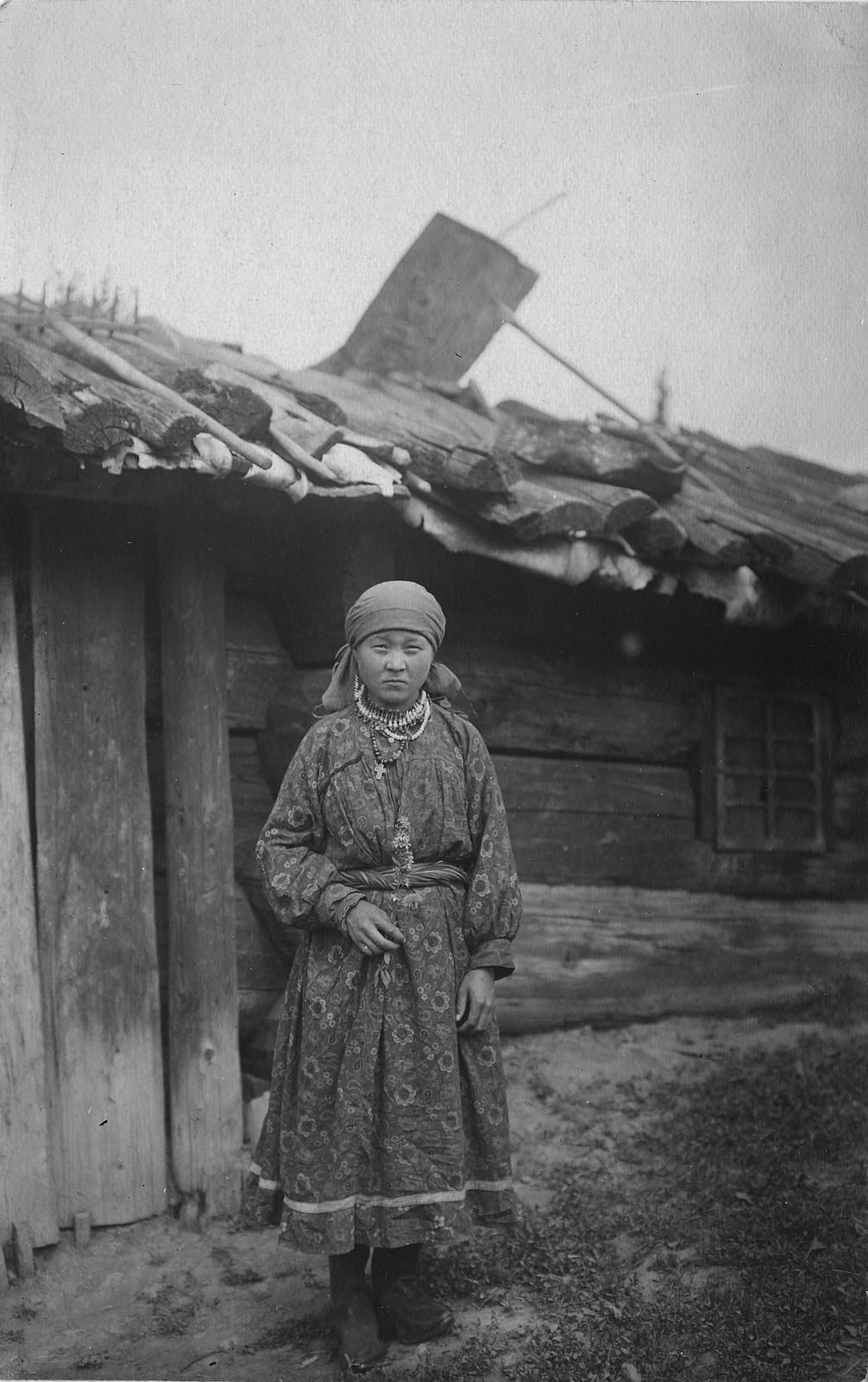 Молодая девушка в традиционной одежде у юрты