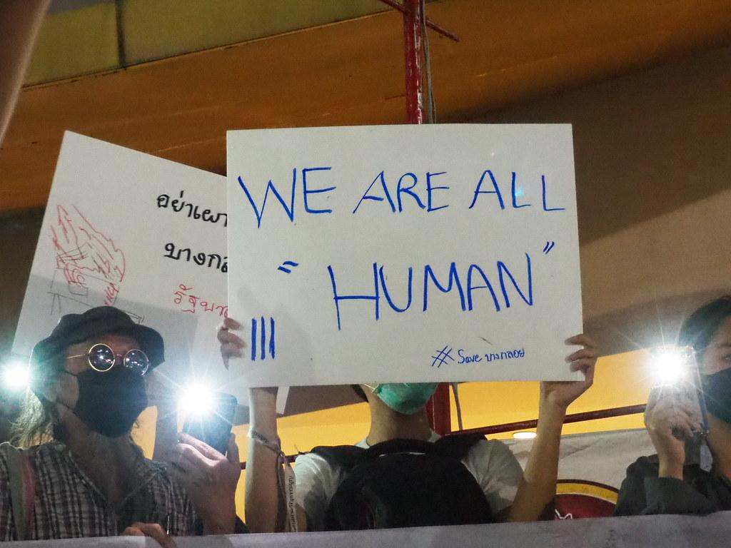 """ผู้ชุมนุมถือป้าย """"We are all human"""" ในการชุมนุมที่หน้าหอศิลปวัฒนธรรมแห่งกรุงเทพมหานคร"""