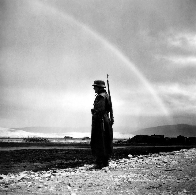 A Rainbow adorns the sky while a German soldier keeps watch during WW2