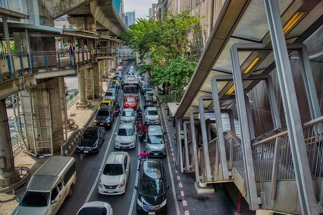 Traffic on Silom road with BTS Skytrain tracks above in Bangkok, Thailand