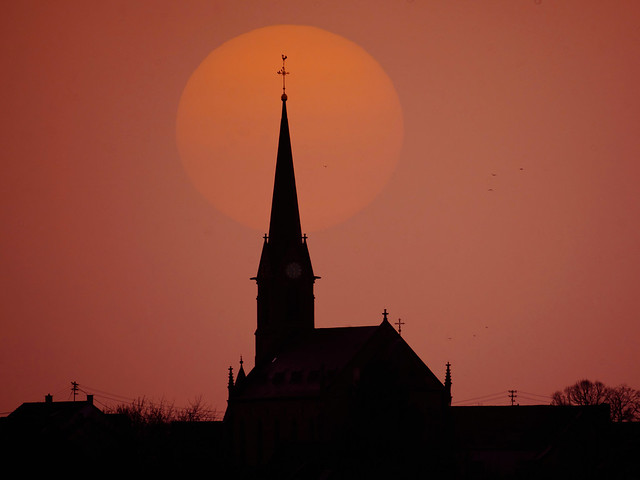 Apocalyptic sunset behind the St. Anna church, Biesingen, Saarland, Germany