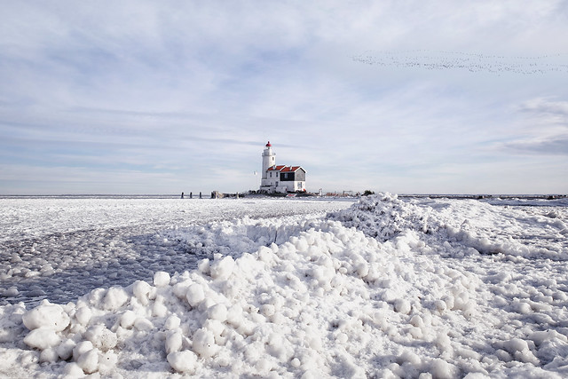 Drifting ice piling up at the lighthouse of Marken