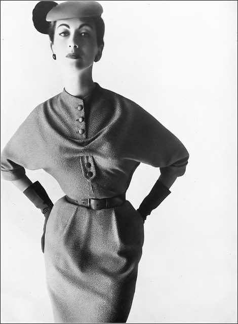 Della Oake in a town dress of gray and white flecked tweed with an important top width, belted in plain leather by Susan Small, silk jersey beret by R.M.Hats, photo by Keith Ewart, Harper's Bazaar UK, October 1953