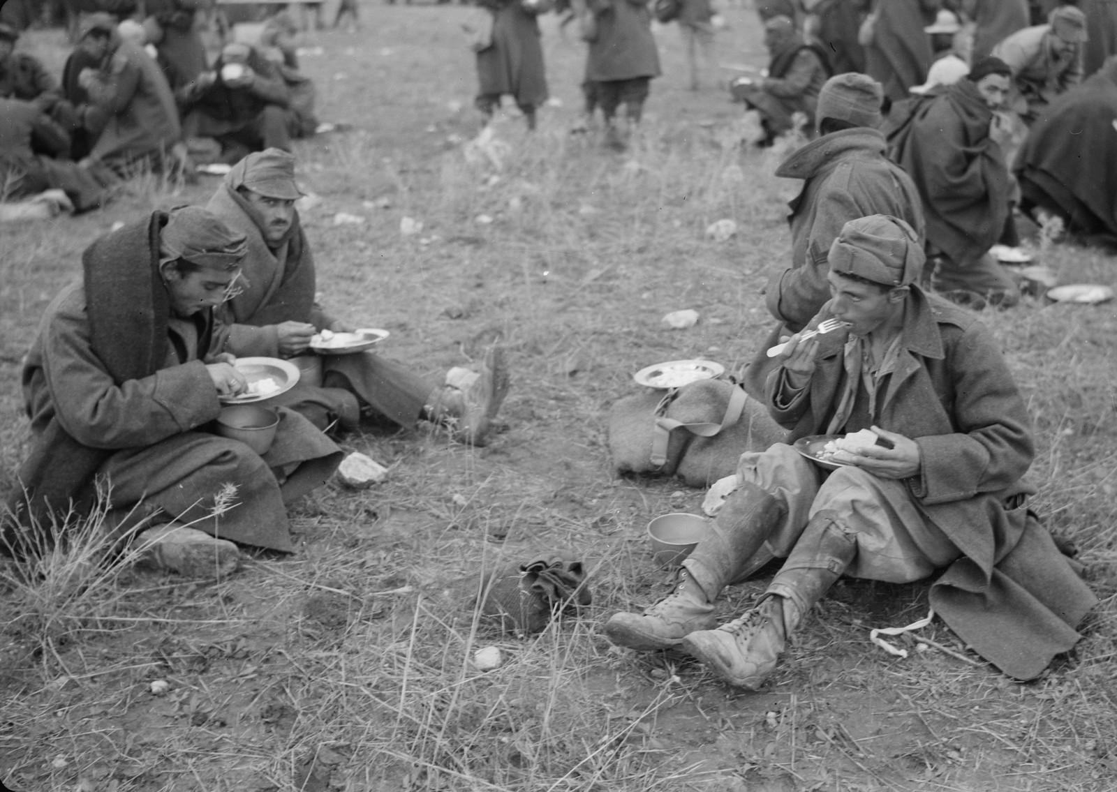 30. Итальянские пленные едят, сидя на земле на станции Вади Сарар