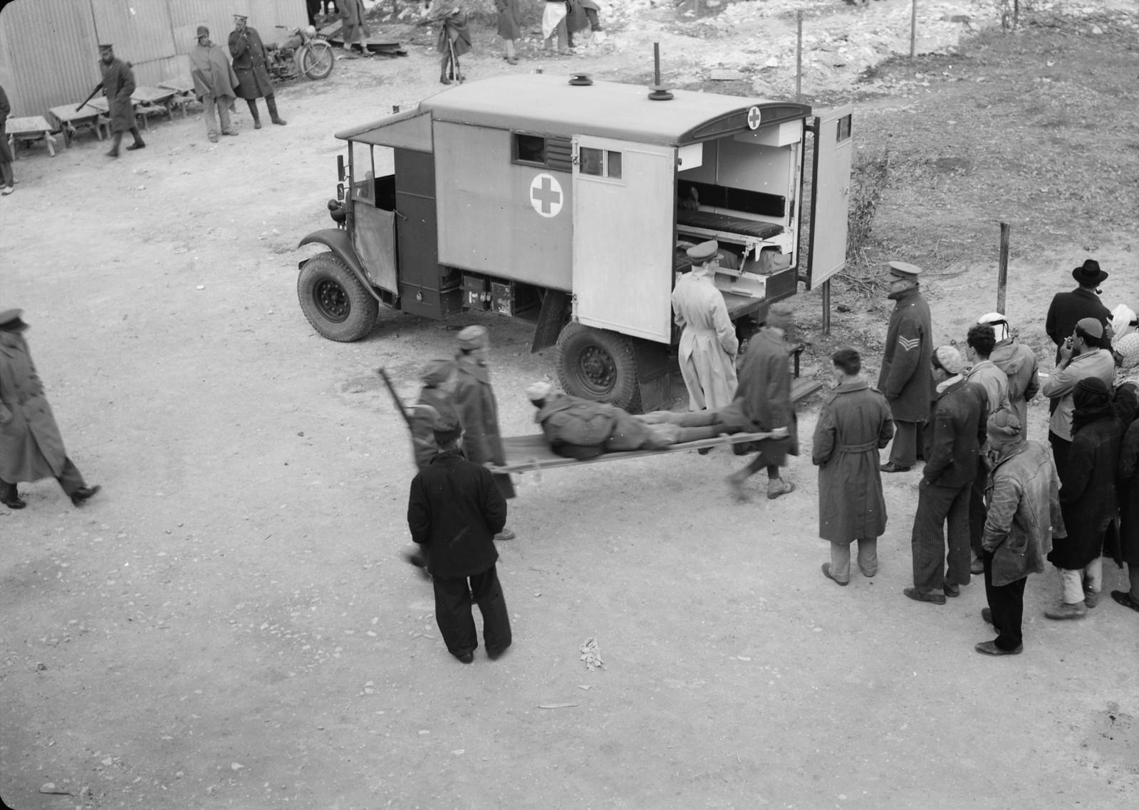 13. Итальянские пленные грузят носилки с раненым товарищем в британскую санитарную машину.