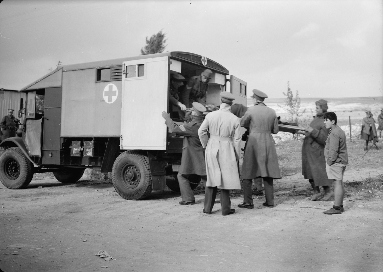 14. Итальянские пленные грузят носилки с раненым товарищем в британскую санитарную машину