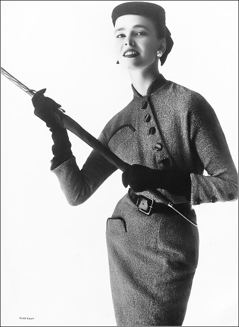 Susan Abraham in black-and-white tweed dress with bound pockets fastening diagonally from neck to waist, belted in leather, by Young Lomdoner, felt toque by Harvane, photo by Keith Ewart, Harper's Bazaar UK, October 1953