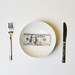 100 dollar banknote on white plate with fork and knife