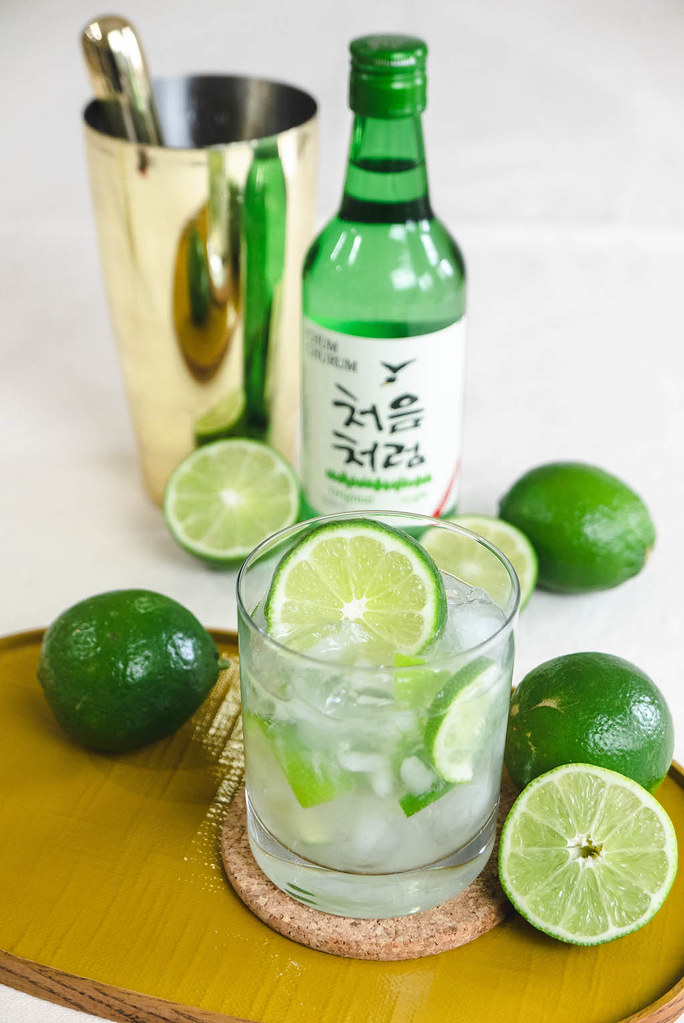 An overhead side shot of a soju bottle, a cocktail shaker, and the clear cocktail with limes.