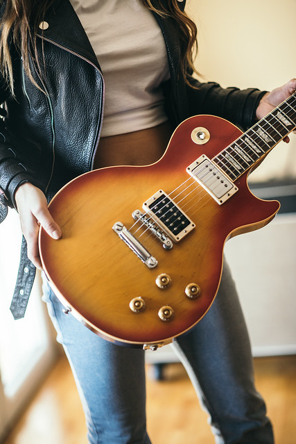 Young rock girl in leather jacket holding electric guitar closeup.