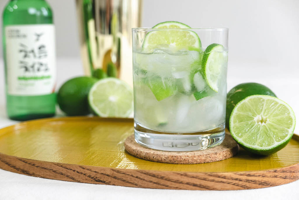 A Glass of Soju Caipirinha sitting on a yellow tray. Limes surround the drink.