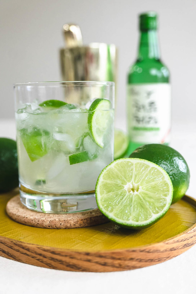 A side shot of soju cocktail. Muddled lime, sugar, and soju with crushed ice in a glass.