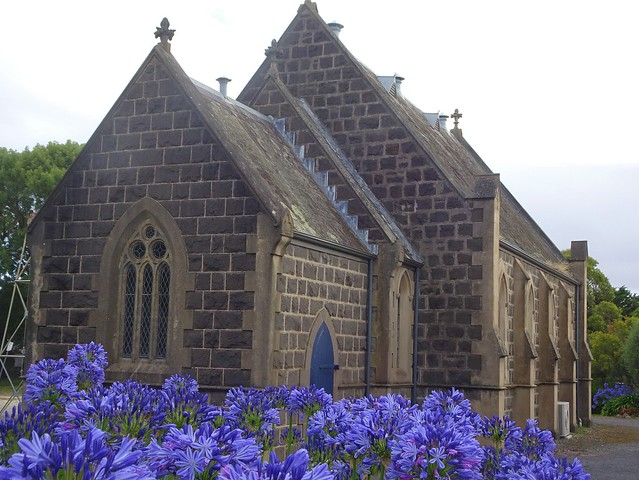 Winchelsea. The fine basalt Presbyterian Church built in Gothic style in 1870. Now the Uniting Church. Agapanthas in front of it.
