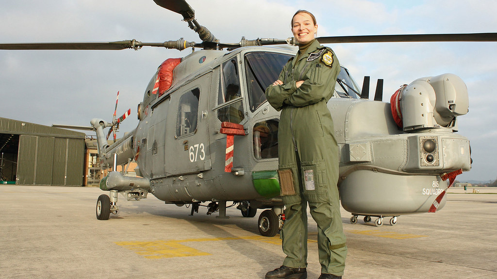 Danielle stands in uniform in front of a helicopter.
