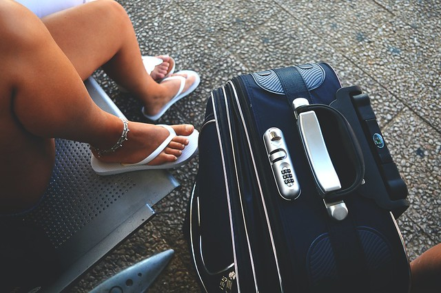 Female sitting next to a suitcase - Stock photo