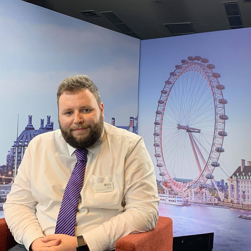 Photo of Andy Long wearing a shirt and tie sitting in front of a stand which has a photo of a big wheel to his right