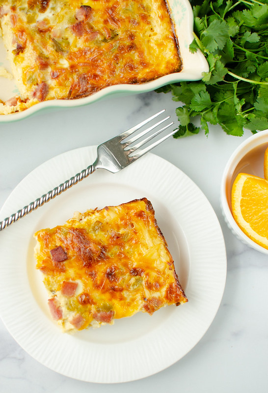 Overhead shot of a slice of ham breakfast casserole on a white plate with a fork; bowl of oranges, bunch of cilantro, and the casserole dish in background
