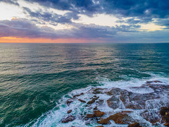 Aerial sunrise seascape with waves and clouds