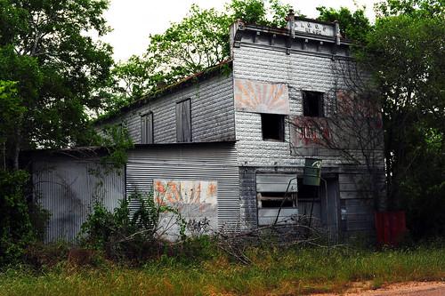 usa texas coloradocounty rockisland ghosttown independentorderofoddfellows 462 abandoned architecture pressedmetalsiding facade decay weathered sign rust ioofno462 highway90a building derelict deerfeeder