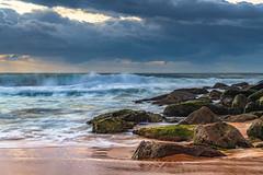 Sunrise seascape with rain clouds on the horizon