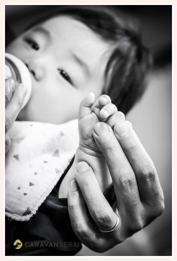 哺乳瓶に入ったミルクを飲む赤ちゃん モノクロ写真