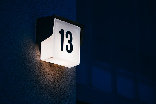 Close-up of a building number. Unlucky number thirteen