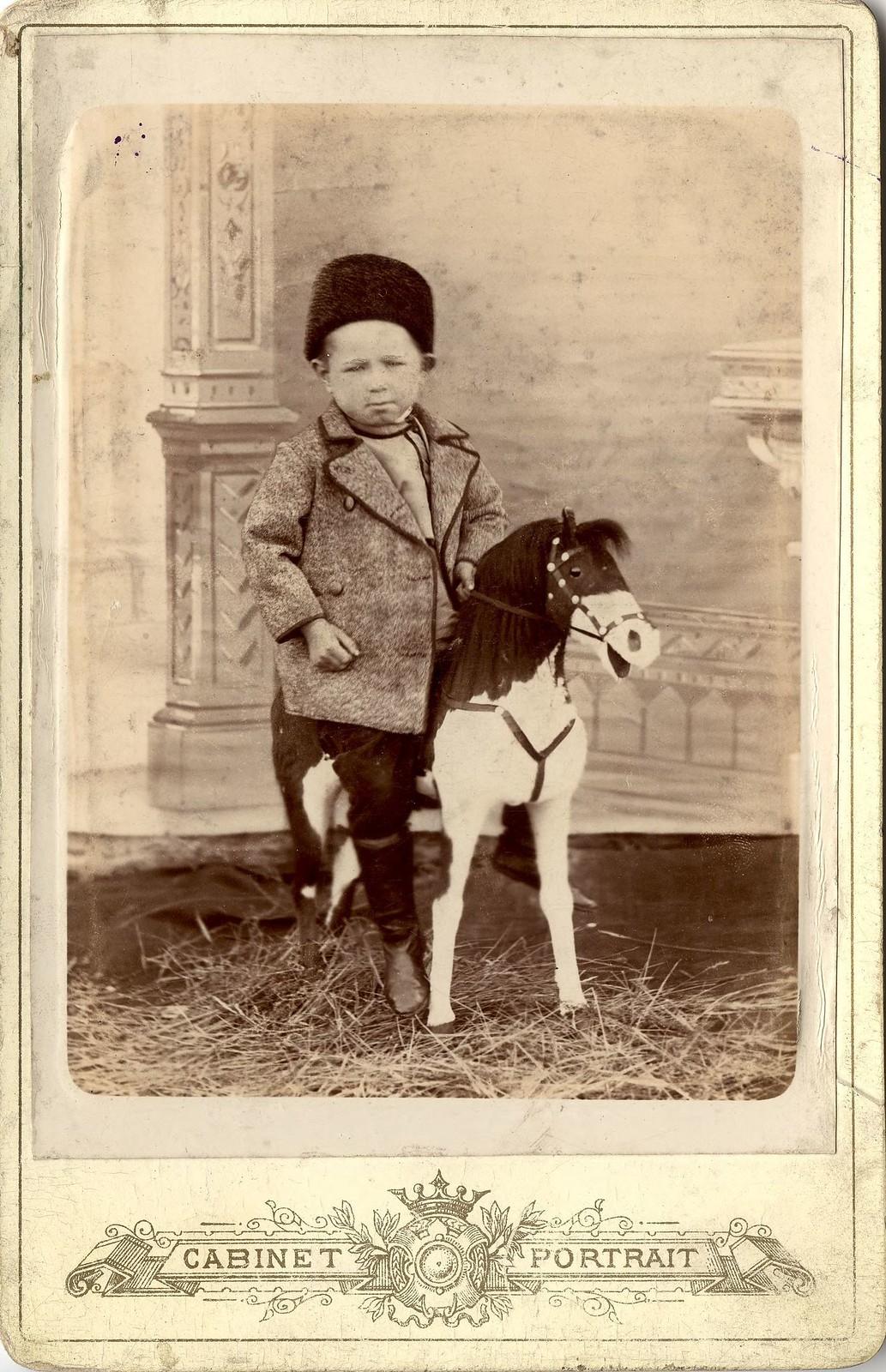 1890. Портрет мальчика, сидящего на игрушечном коне.