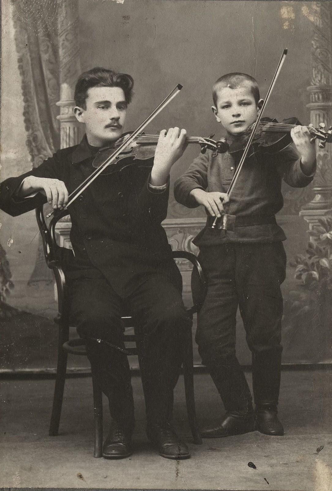 1910. П.Л.Столяров и В.П.Каретников, играющие на скрипках.
