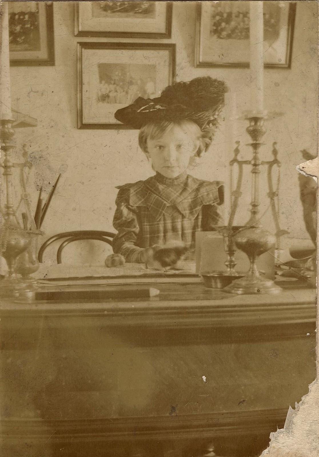 1904. Девочка Гладышева Ольга Ивановна за письменным столом в кабинете.