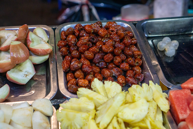 Close Up Food Photo of Plum, Lychee, Apple, Pineapple, Watermelon, Glazed Dates and other Fruits on a Dessert Fruit Bowl Place at a Night Market in Can Tho, Vietnam