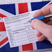 Hand holding a pen and Vaccination record card with flag of United Kingdom
