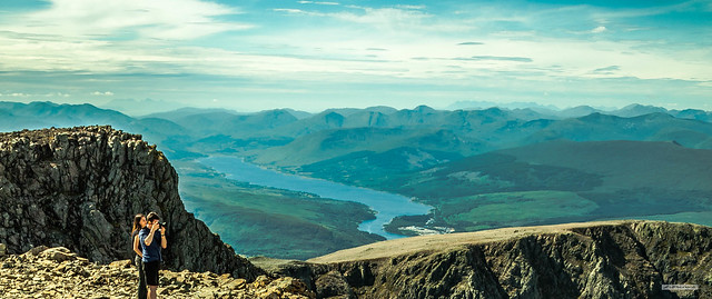 Rocky summit of Ben Nevis with Loch Eil, middle ground, and the mountains of the Isles of Rum and Skye on the furthest horizon.