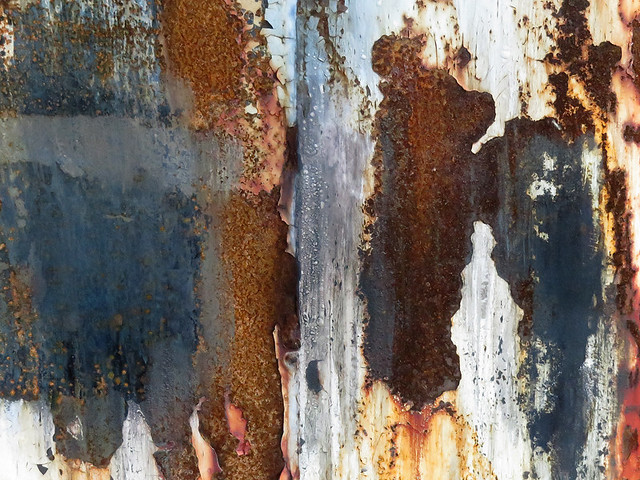 An abstract of a dumpster with patchy rust