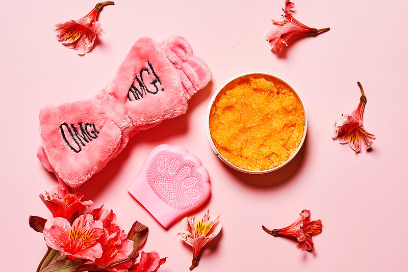 Silicon hand massager and relaxing cream on pink background