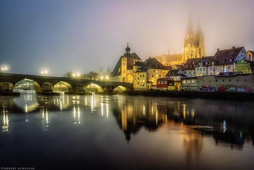 Regensburg: Danube flickers on foggy evening.