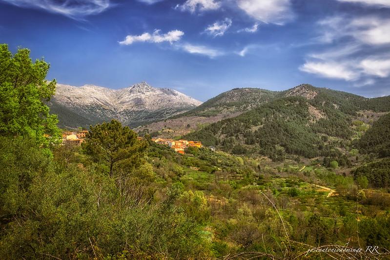 Vegetación, pueblo y montañas.