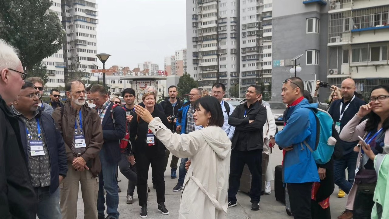 Ming Yang talking to a group of people in the streets of Beijing