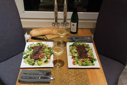 In Rosmarin-Salbei-Butter arosiertes Roastbeef auf einem Bett aus Salat mit Tomaten, Gurken, Zwiebeln sowie Oliven und dazu frisch gebackenes Ciabatta (Tischbild)