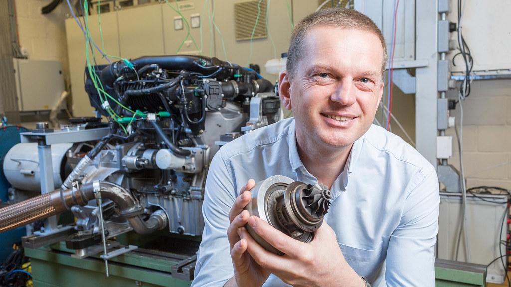 Professor Chris Brace holds up an engine part