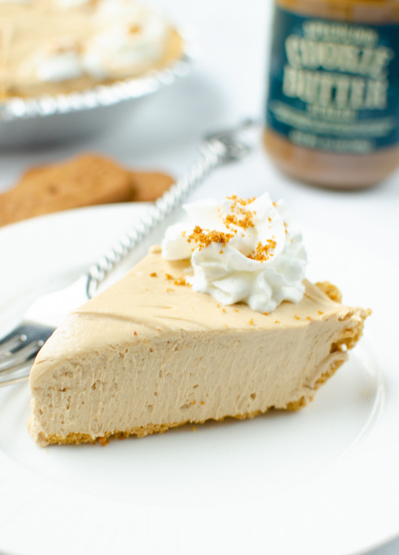 Slice of cookie butter pie on a white plate with a fork; jar of cookie butter, 2 cookies, and the rest of the pie in the background