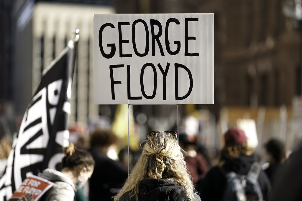 A protester holds a George Floyd sign outside the Hennepin County Courthouse in downtown Minneapolis, Minnesota