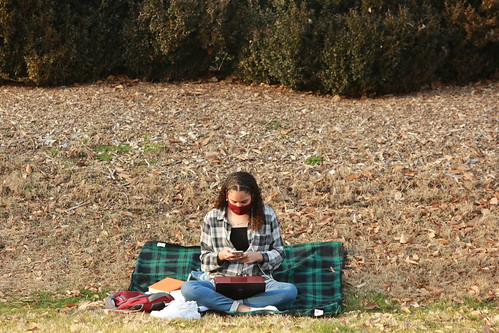 Catching up on her reading while enjoying the fresh air and sunshine in the Sunken Garden.