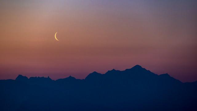 Une lune timide fait son apparition de bon matin au-dessus des Alpes.