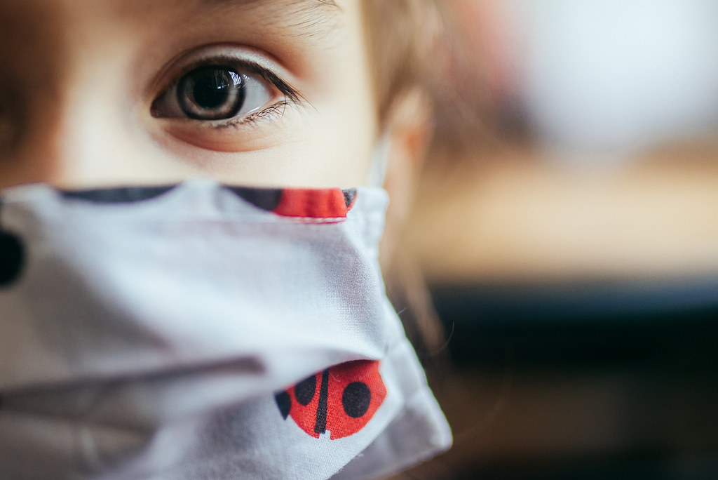 Little girl with protective mask looking at camera. Closeup of eye.
