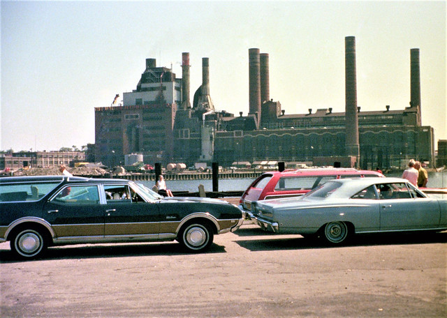 Large colorful 1960s and 70s station wagons line up for a ride on the Bridgeport to Port Jefferson Ferry during a sunny summer day. The old United Illuminating power plant across the harbor was imploded in 1996. Bridgeport CT. Aug 1973