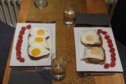Fleischkäse mit Spiegeleiern auf frischem Roggenmischbrot (Tischbild)