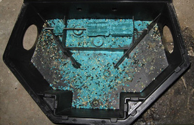 Photo shows the inside of a rodent bait station that contains green blocks of bait and some bait spilled on the bottom. Black droppings of different sizes are visible.