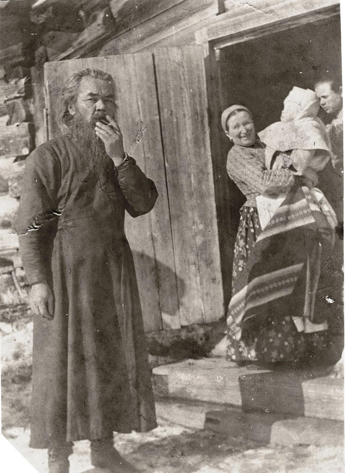 14. Священник Подгорбунский на пороге деревянного дома
